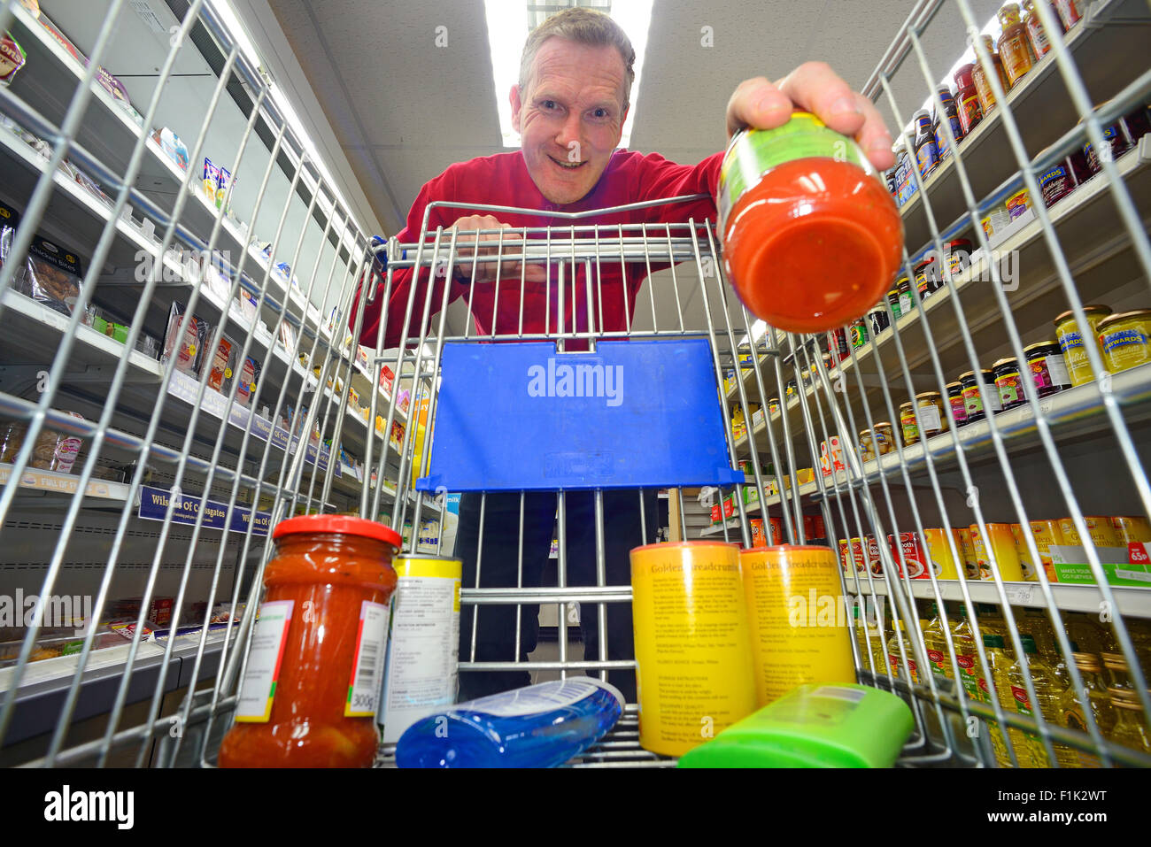 man shopping using trolley in supermarket - Stock Image
