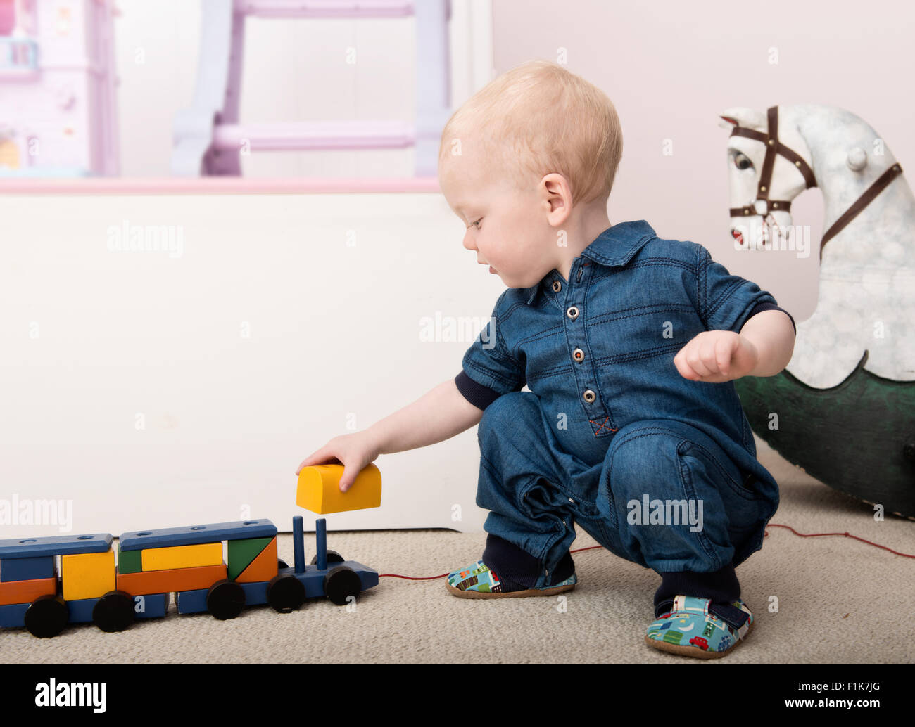 Smiling infant plays with toy train on playroom floor - Stock Image