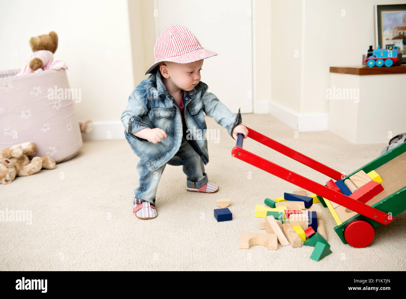 Infant boy wearing a hat plays with toys on the floor of a playroom - Stock Image