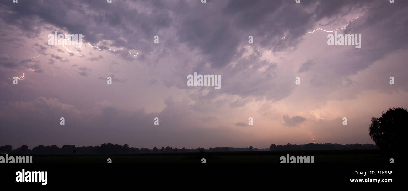 Thunder and lightning at the end of a hot and moistly summer day in the Netherlands - Stock Image