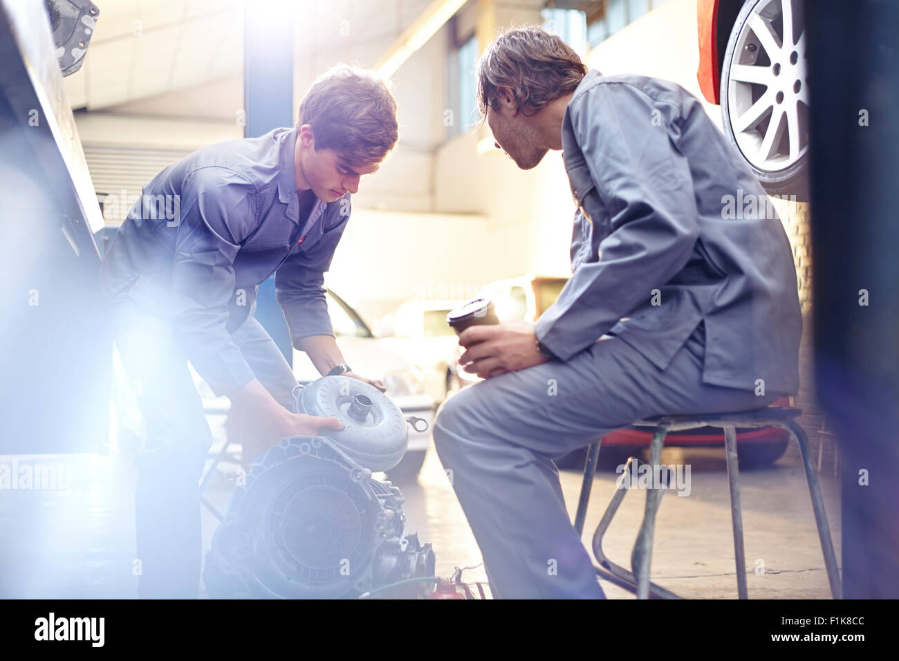 Mechanics examining engine part in auto repair shop - Stock Image