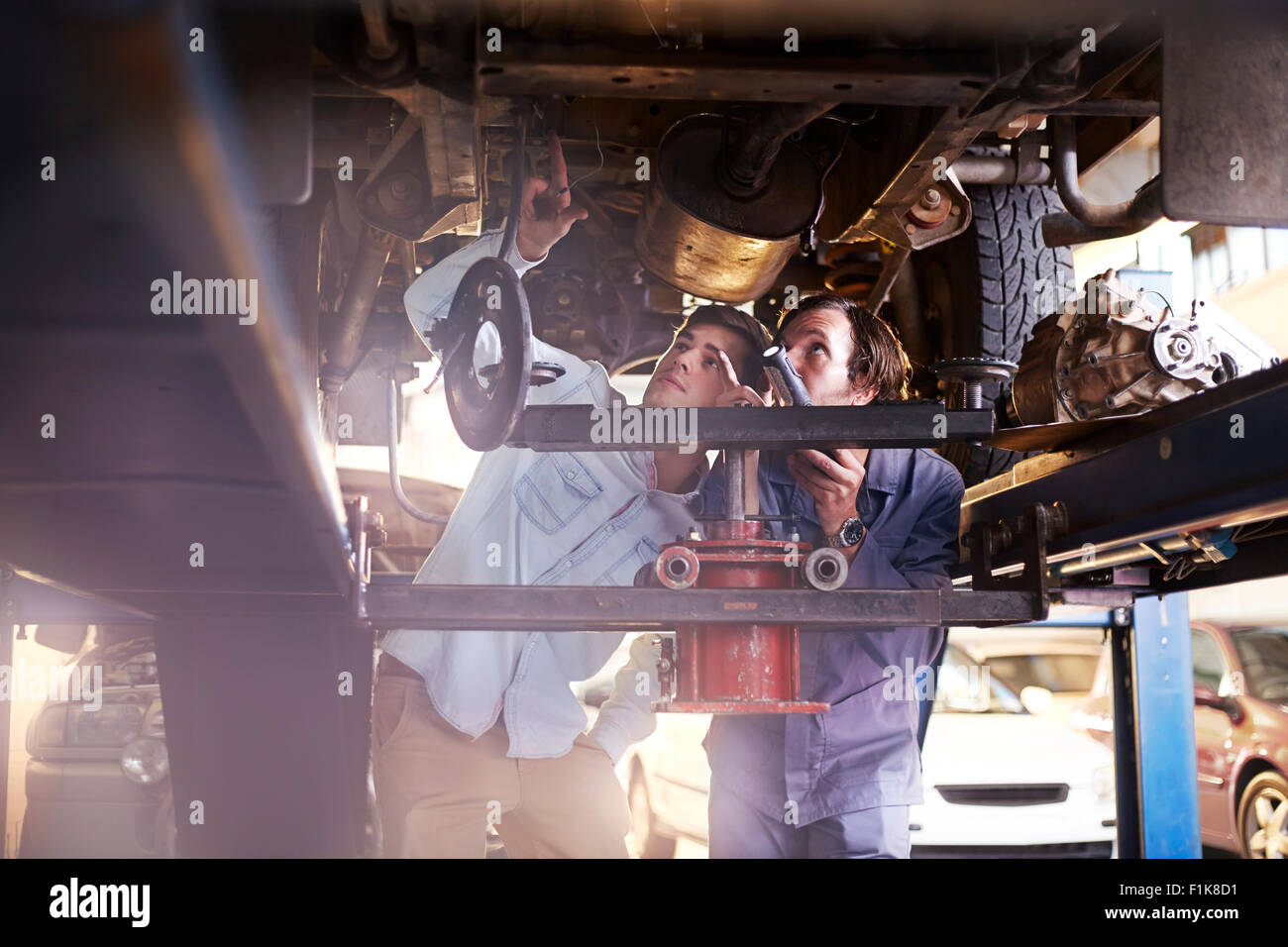 Mechanic and customer under car in auto repair shop Stock Photo