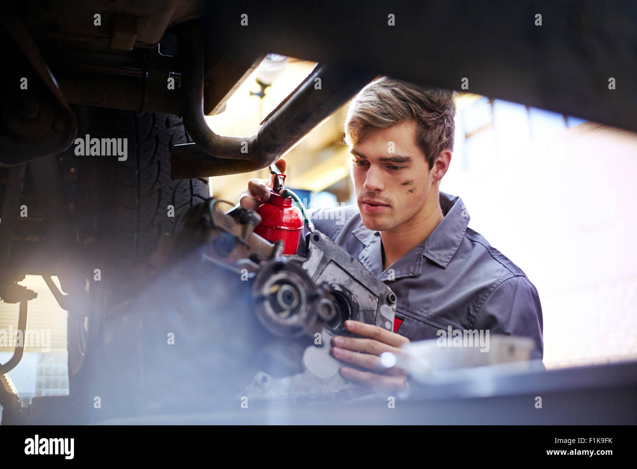 Mechanic oiling part in auto repair shop - Stock Image