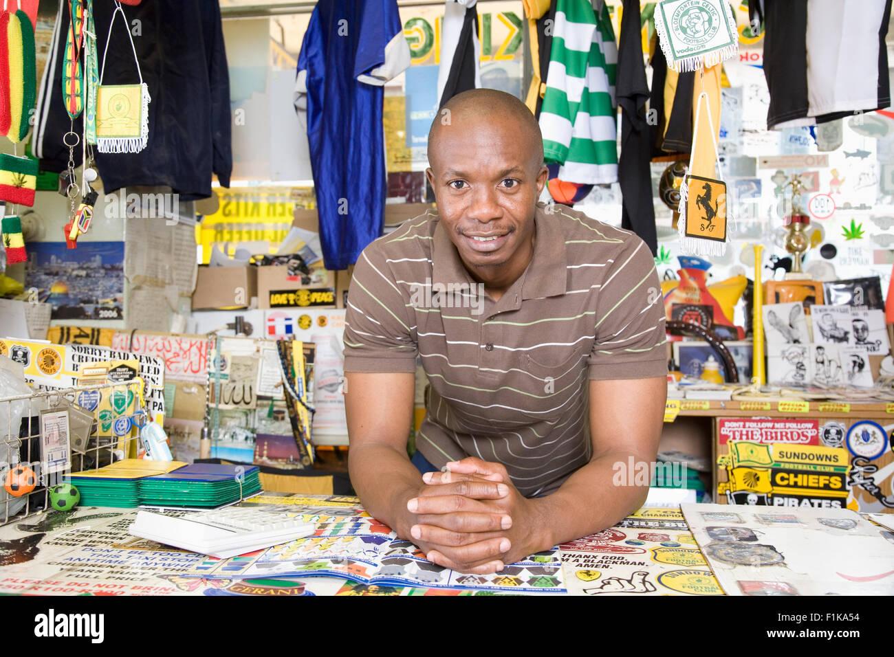 Man selling soccer memorabilia in spaza shop - Stock Image