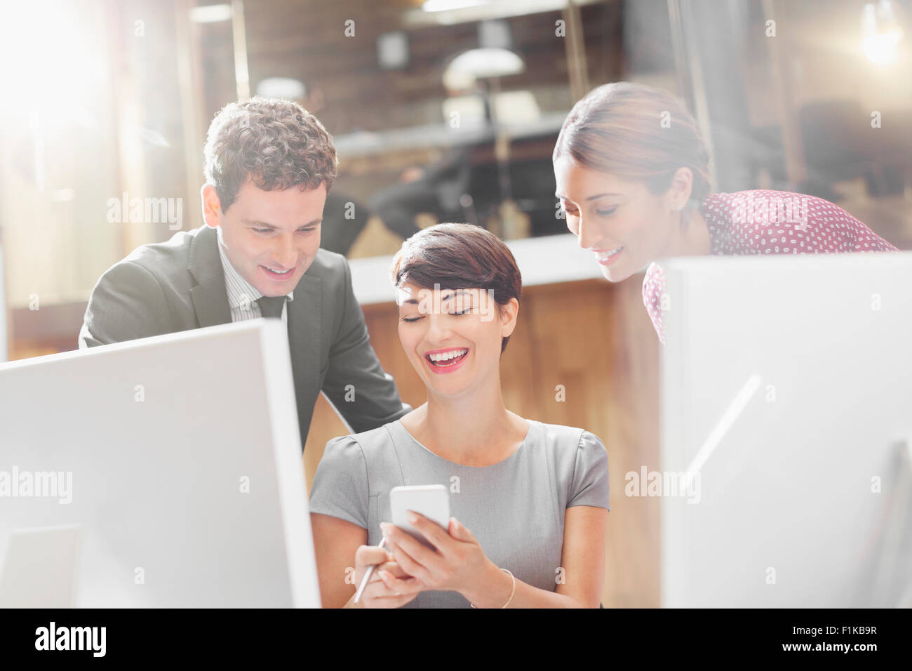 Business people texting with cell phone in office - Stock Image