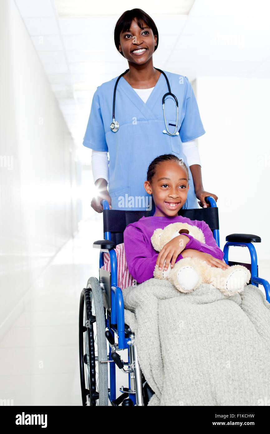 A doctor pushing a girl holding a teddy in a wheelchair - Stock Image