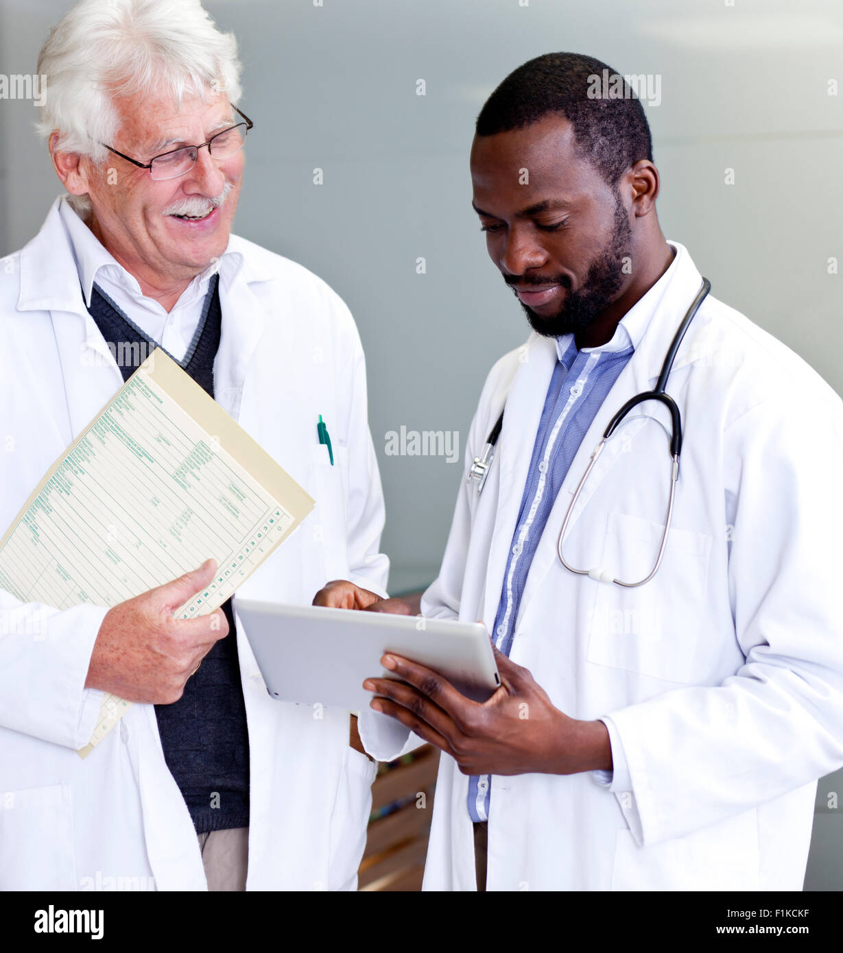 Two doctors going over reports on a tablet - Stock Image