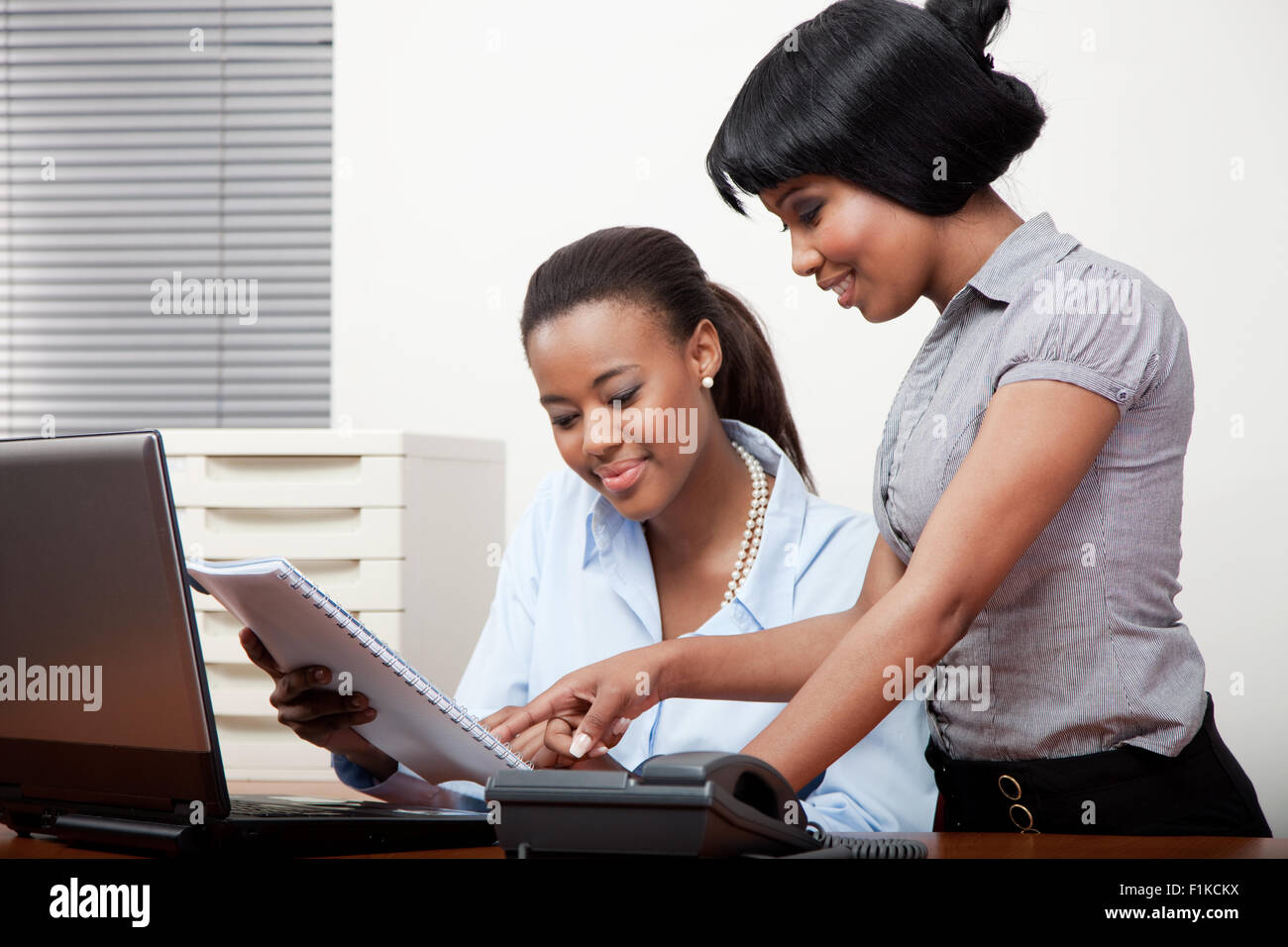 Two Black Women Working Together At An Office Desk Stock