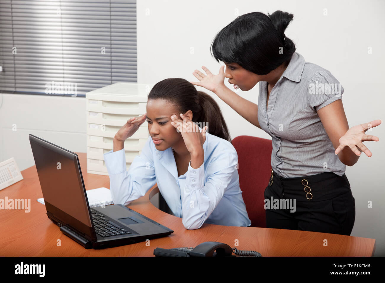 19e722c03b36 A black woman at an office desk being disciplined by her boss Stock ...
