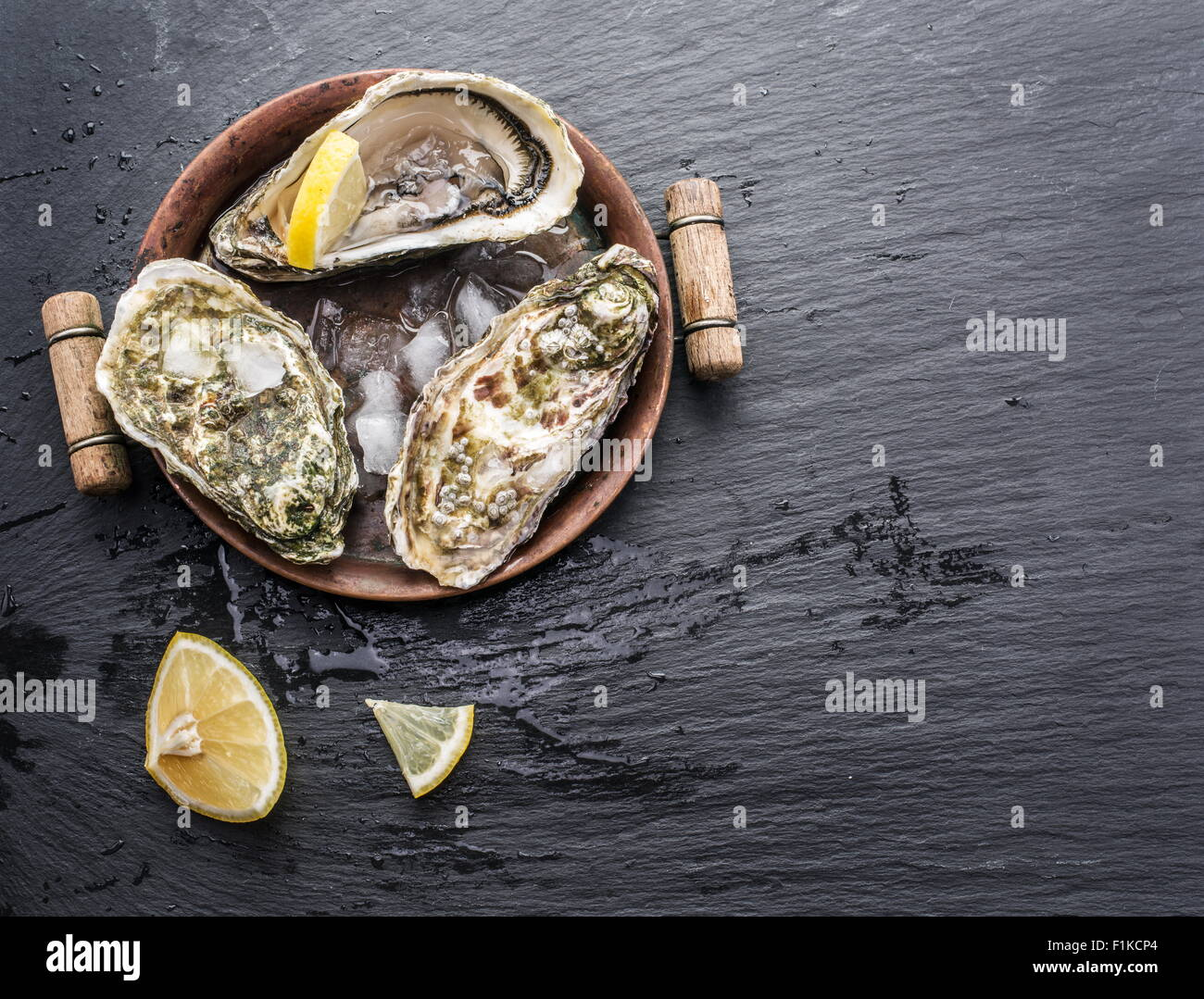 Raw oysters on the graphite board. - Stock Image