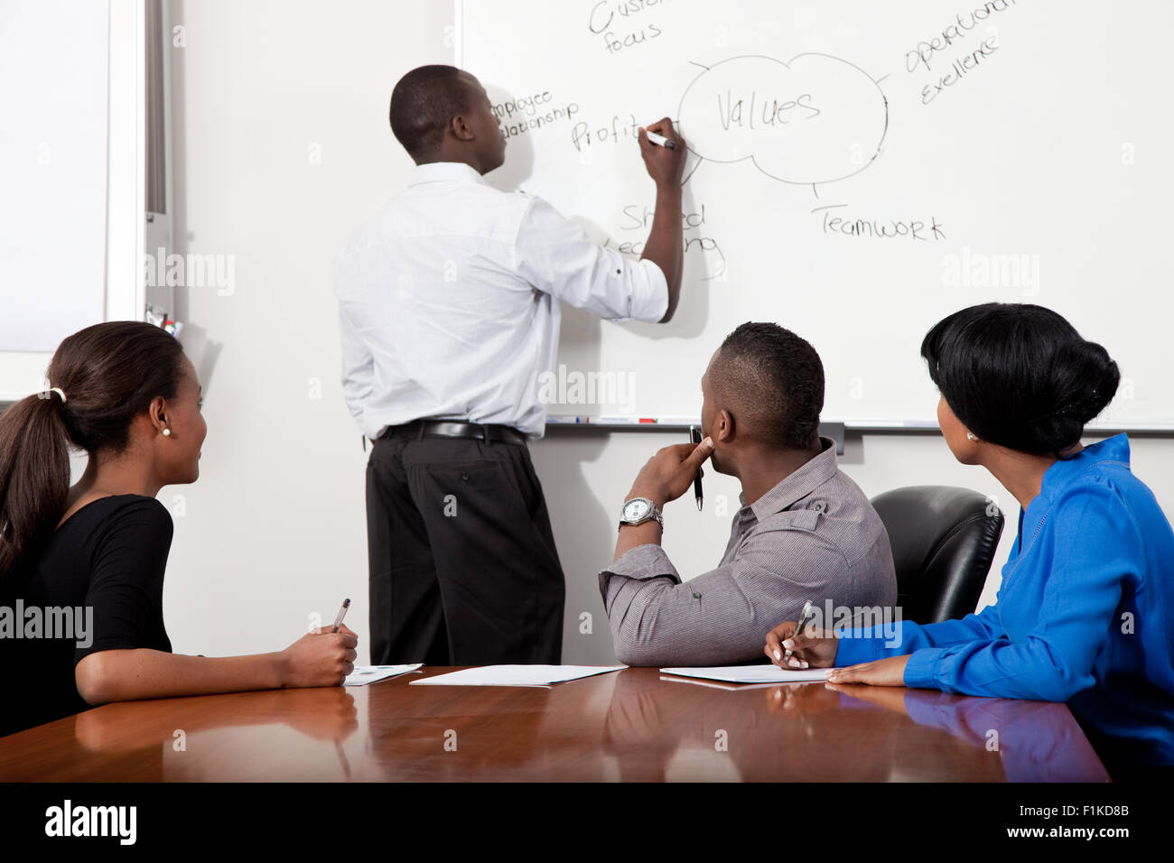 Overall shot of a boardroom meeting involving black business people - Stock Image