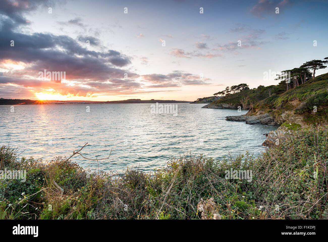 The view from St Anthony's Head in Cornwall with sunset over Falmouth in the far left and St Mawes Castle in - Stock Image