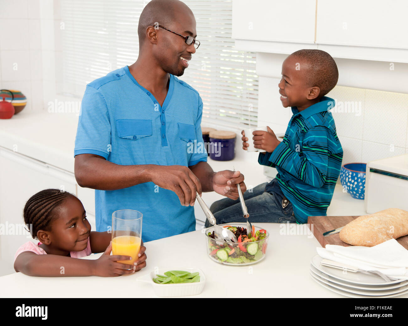 Young African father making food in the kitchen with his children ...