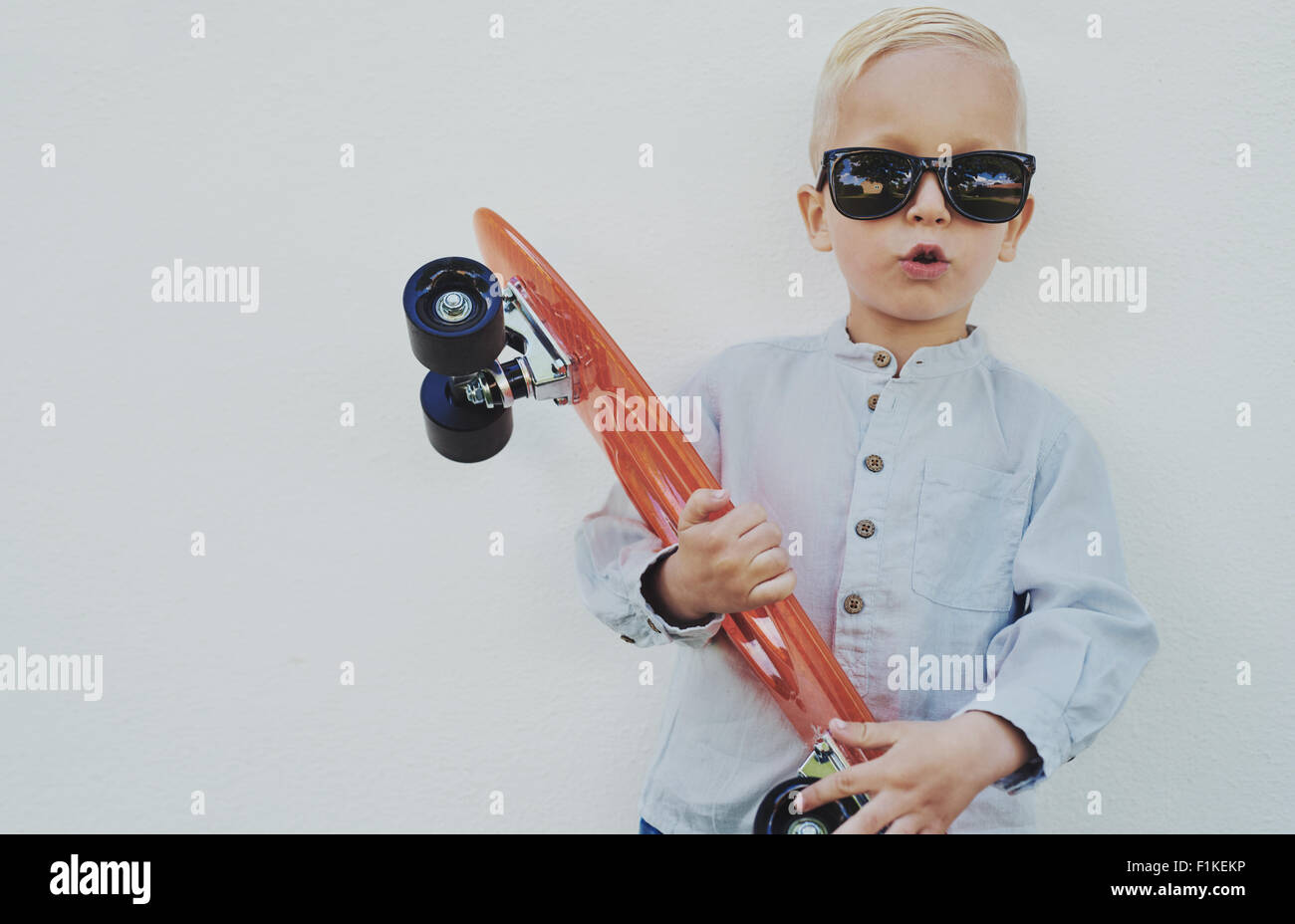 Adorable hipster little boy with a skateboard wearing borrowed sunglasses from his Mum or Dad standing against a - Stock Image
