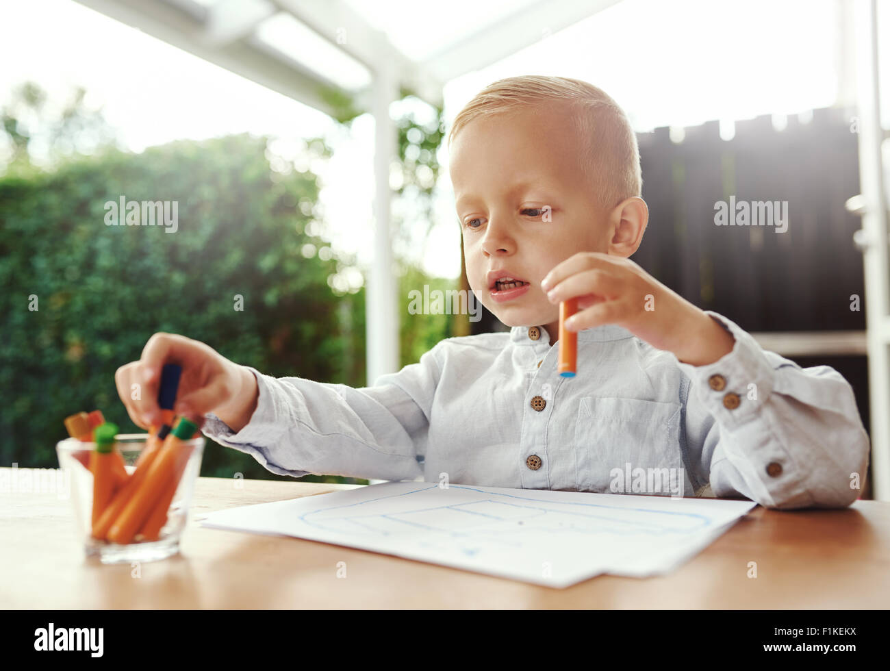 Cute little blond boy selecting a colored wax crayon from a collection in a glass container as he prepares to commence - Stock Image