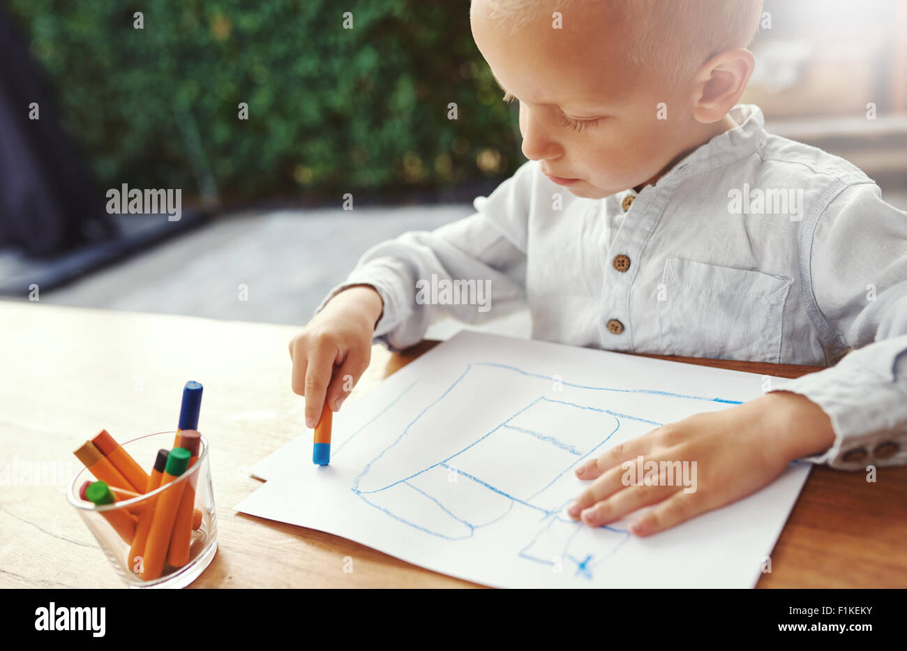 Small boy entertaining himself on a hot summer day standing at a table on an outdoor patio drawing with colored - Stock Image