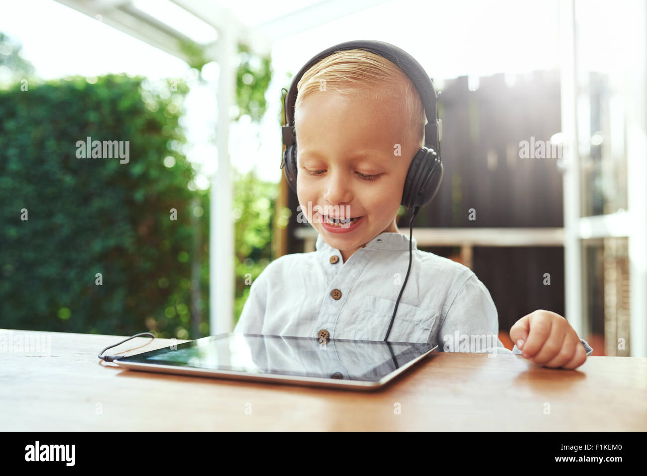 Happy laughing little boy listening to music on his tablet-pc through stereo headphones as he sits outdoors on a - Stock Image
