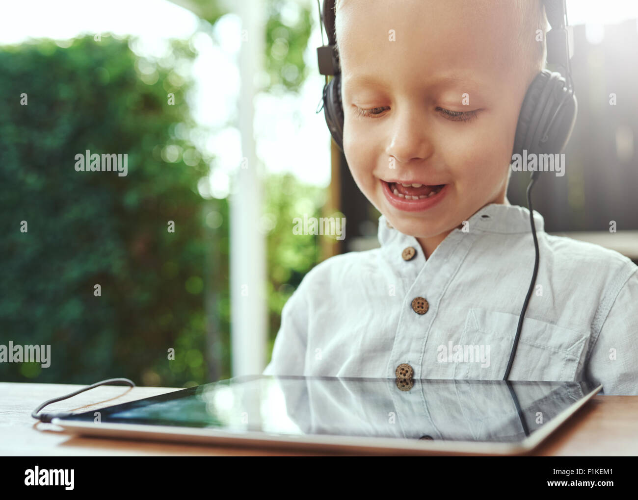 Adorable little boy listening to recorded music on his tablet computer using headphones with a delightful smile - Stock Image