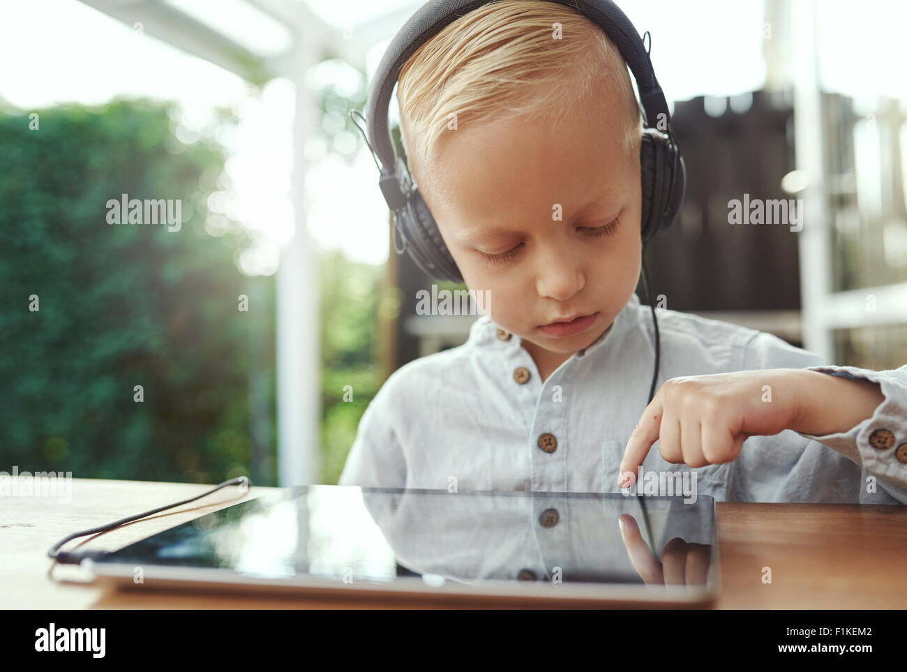 Pensive little boy selecting a new soundtrack from his music library on his tablet computer as he sits outdoors - Stock Image