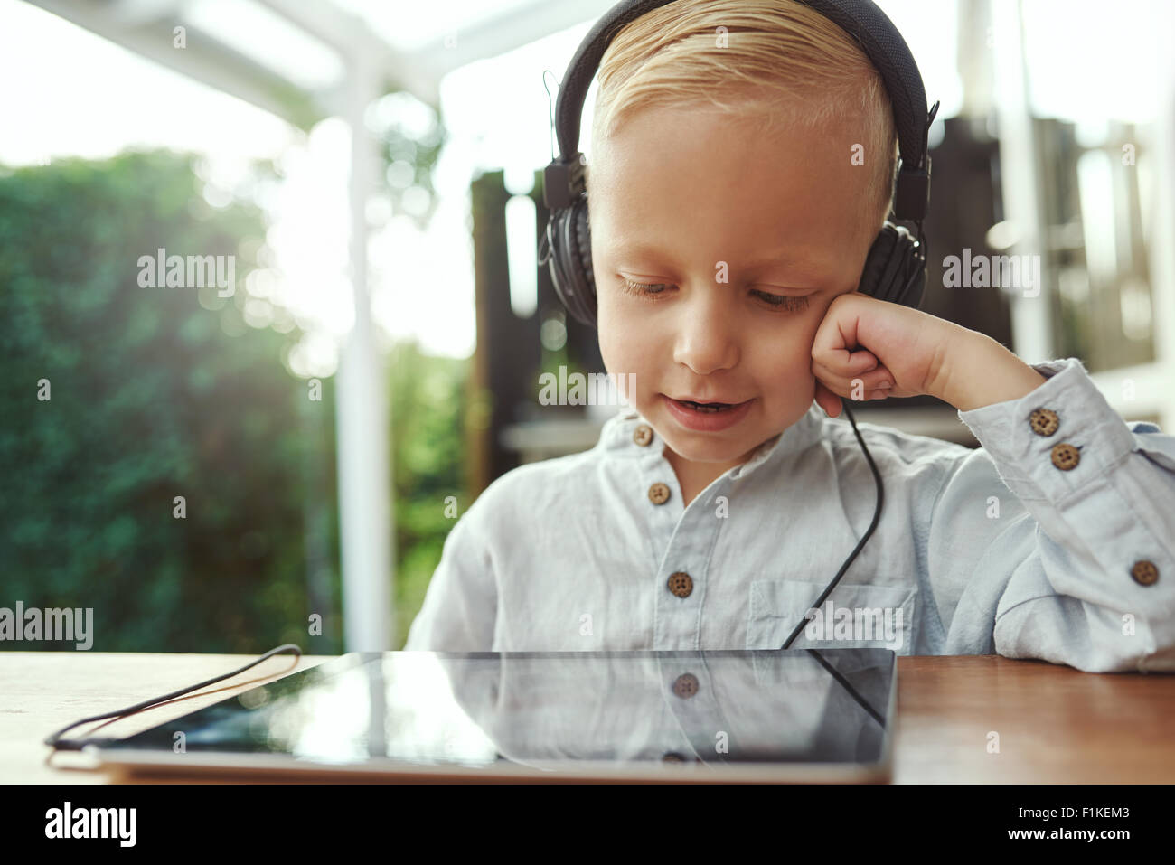 Adorable young boy sitting with a tablet computer listening to his music library with a happy smile of contentment - Stock Image