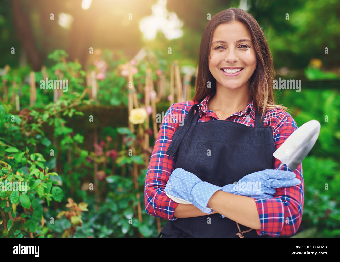 Smiling successful young nursery owner standing amongst her plants with folded arms and a trowel in her hands beaming - Stock Image