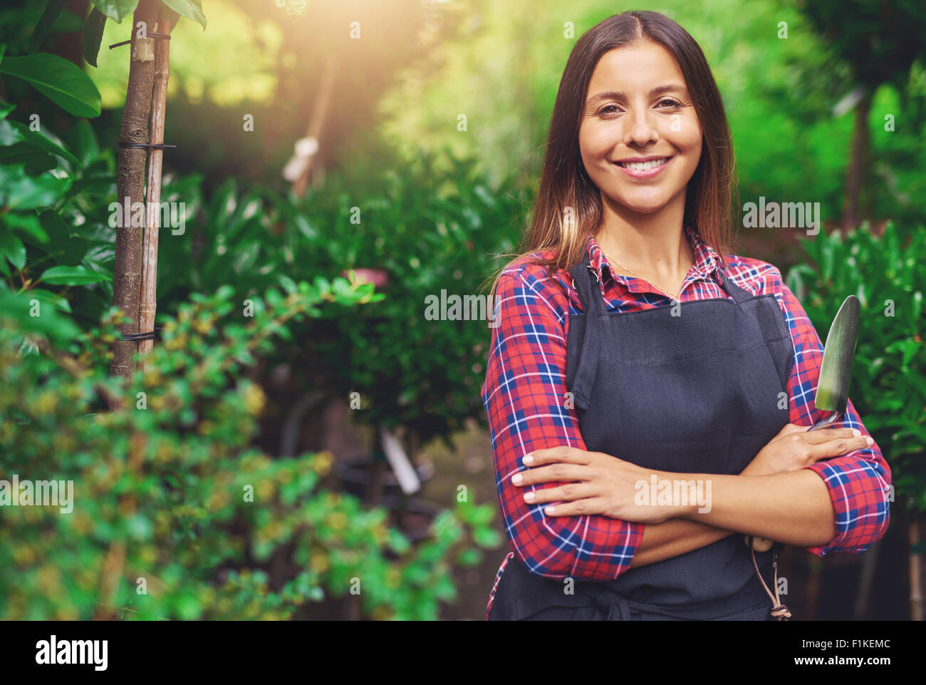 Smiling happy young woman enjoying her garden standing with folded arms against lush greenery with a trowel in her - Stock Image