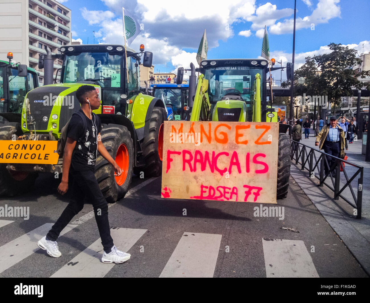 Paris, France. French Farmers Demonstration with 1000's Tractors, teenager walking past French protest poster - Stock Image