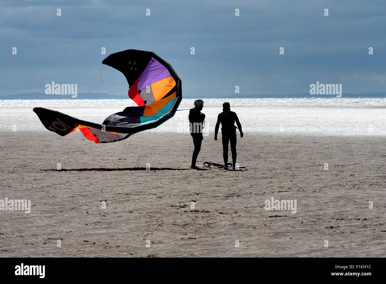 Two kitesurfers with equipment on the sandy beach at St Annes in Lancashire - Stock Image