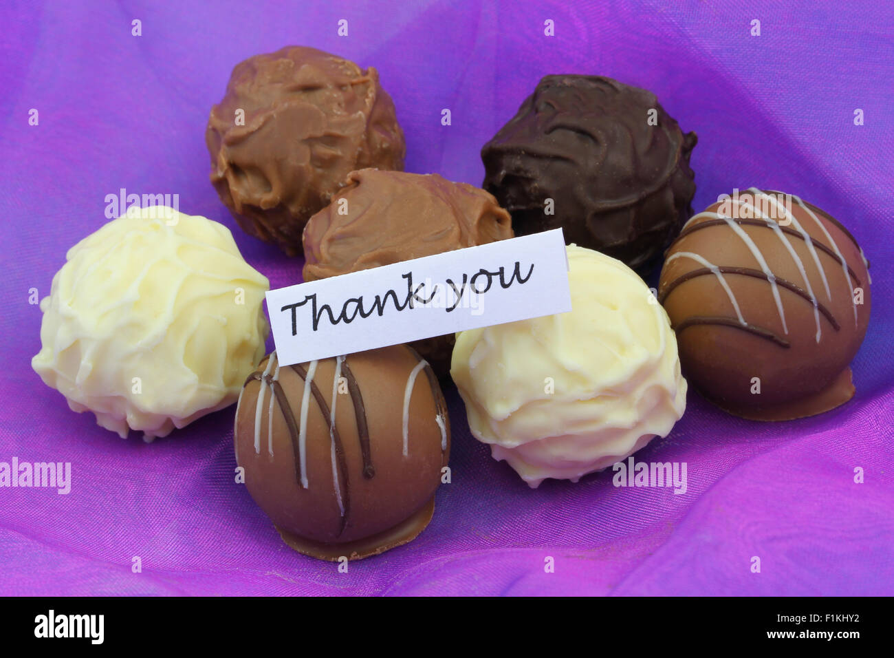 thank you card with assorted chocolates on purple background stock