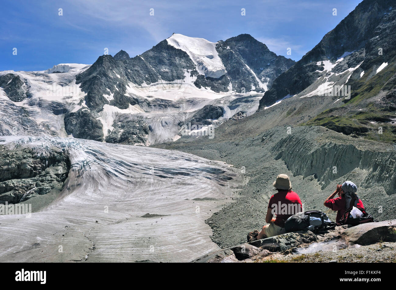 Mountain walkers / Hikers resting with view over the Moiry Glacier in the Pennine Alps, Valais / Wallis, Switzerland - Stock Image