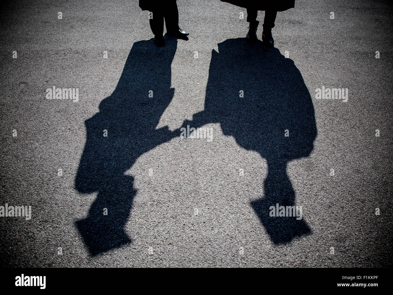 The shadows of two young students on graduation day at University of Birmingham, England. - Stock Image