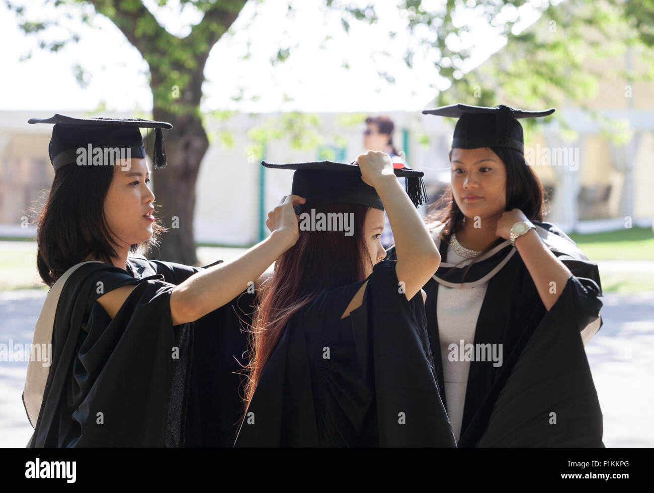Three young overseas graduates in gowns and caps at University of Birmingham on graduation day. - Stock Image