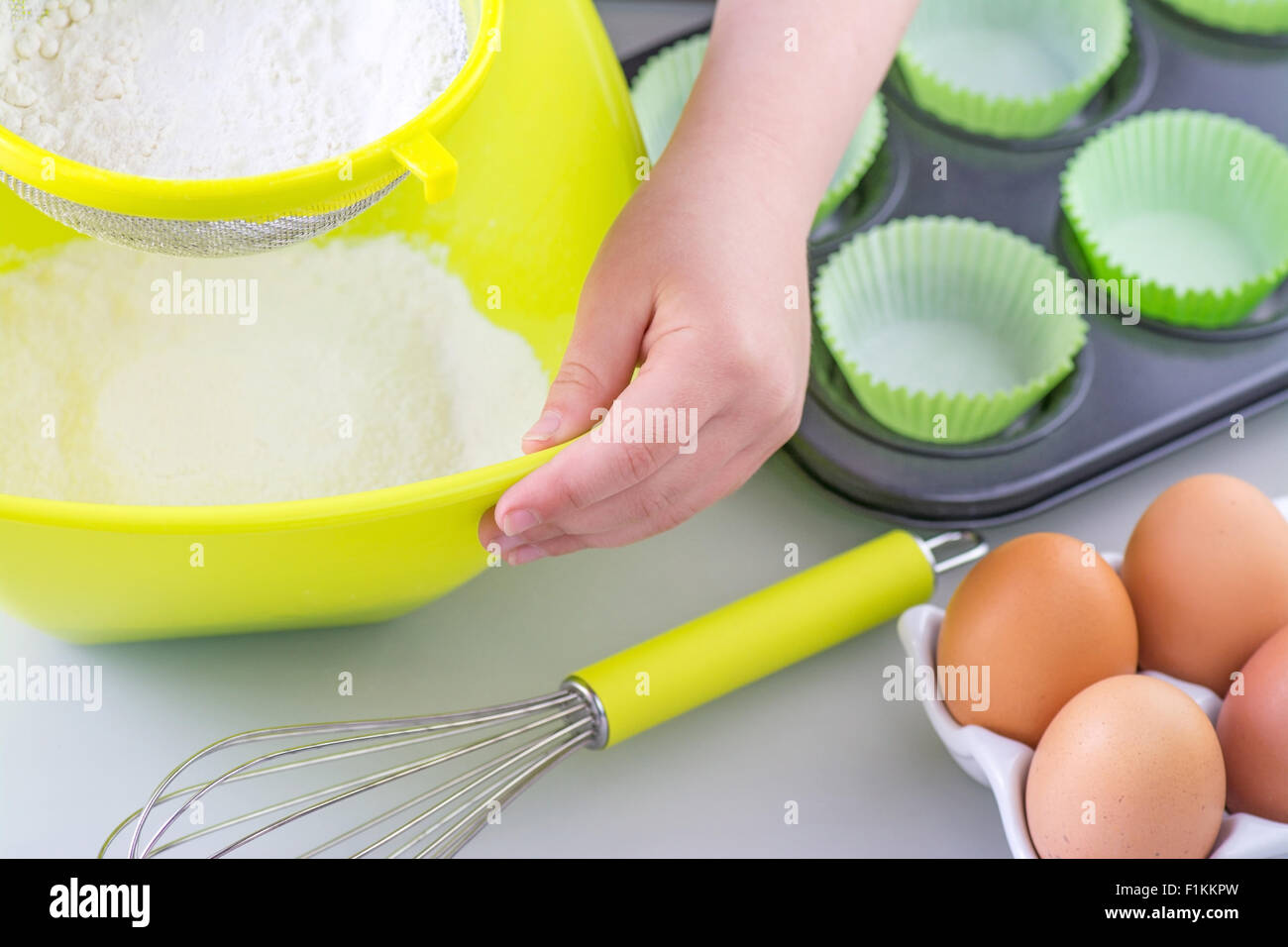 Child sieving flour into a bowl in preparation for  cooking cake, room for text - Stock Image