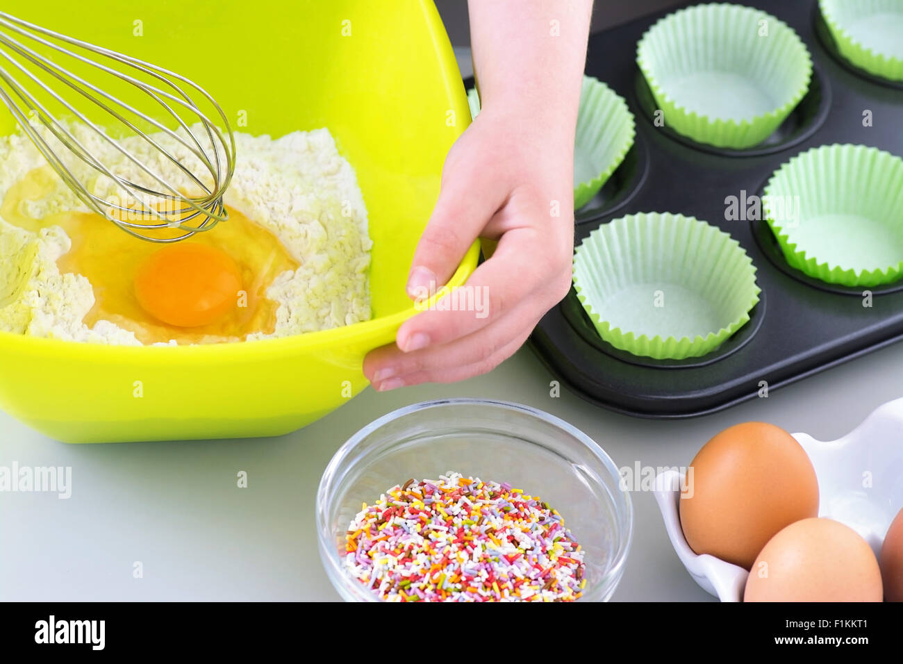 Boy or Girl Baking  cooking cakes just about to whisk the egg into the flour - Stock Image