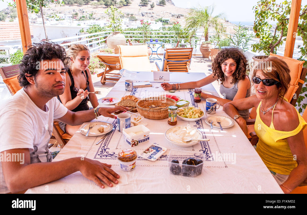Family Having Breakfast on The Roof of A Villa in Lindos Rhodes Greece - Stock Image