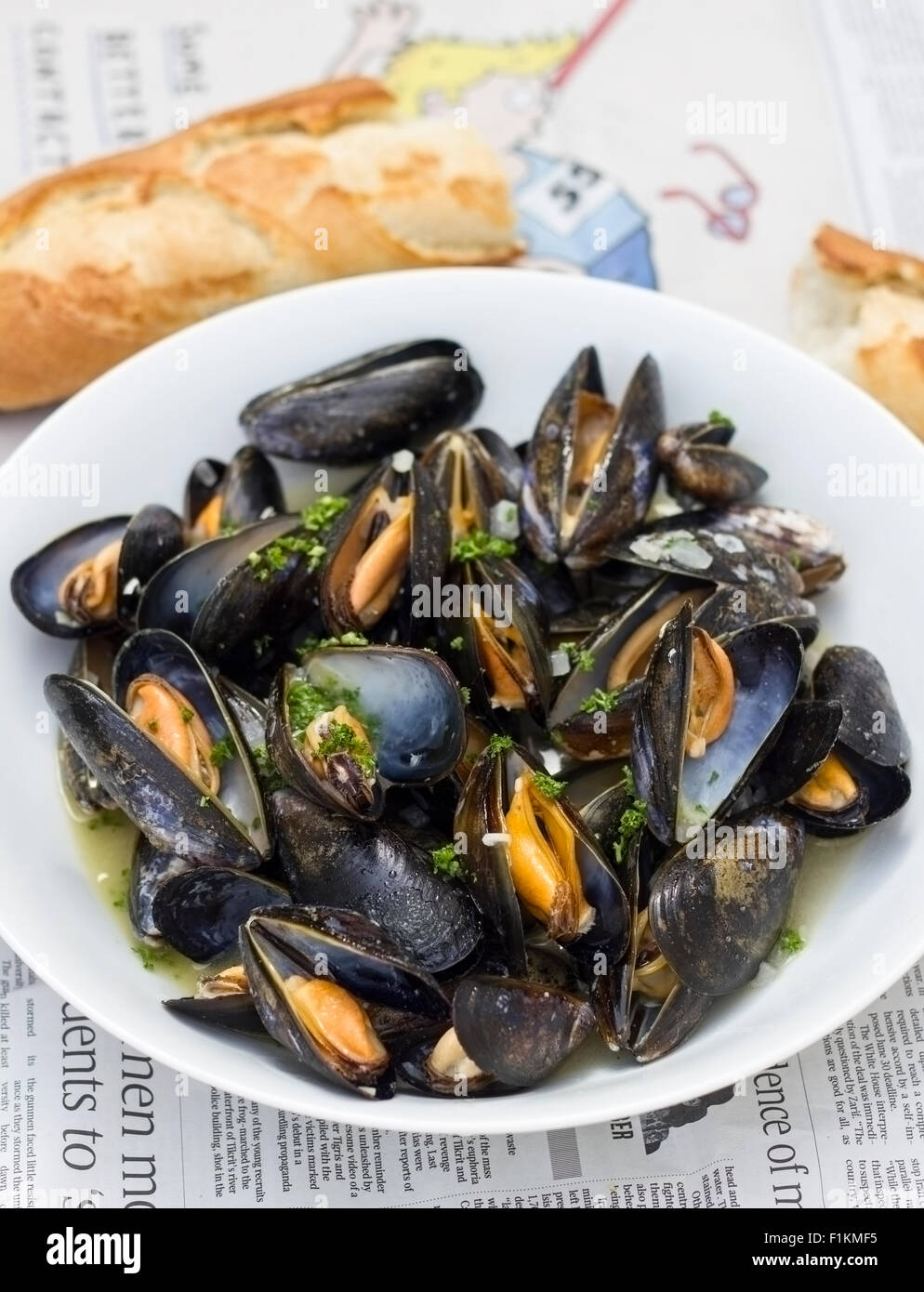 A bowl of moules marinière with baguette - Stock Image
