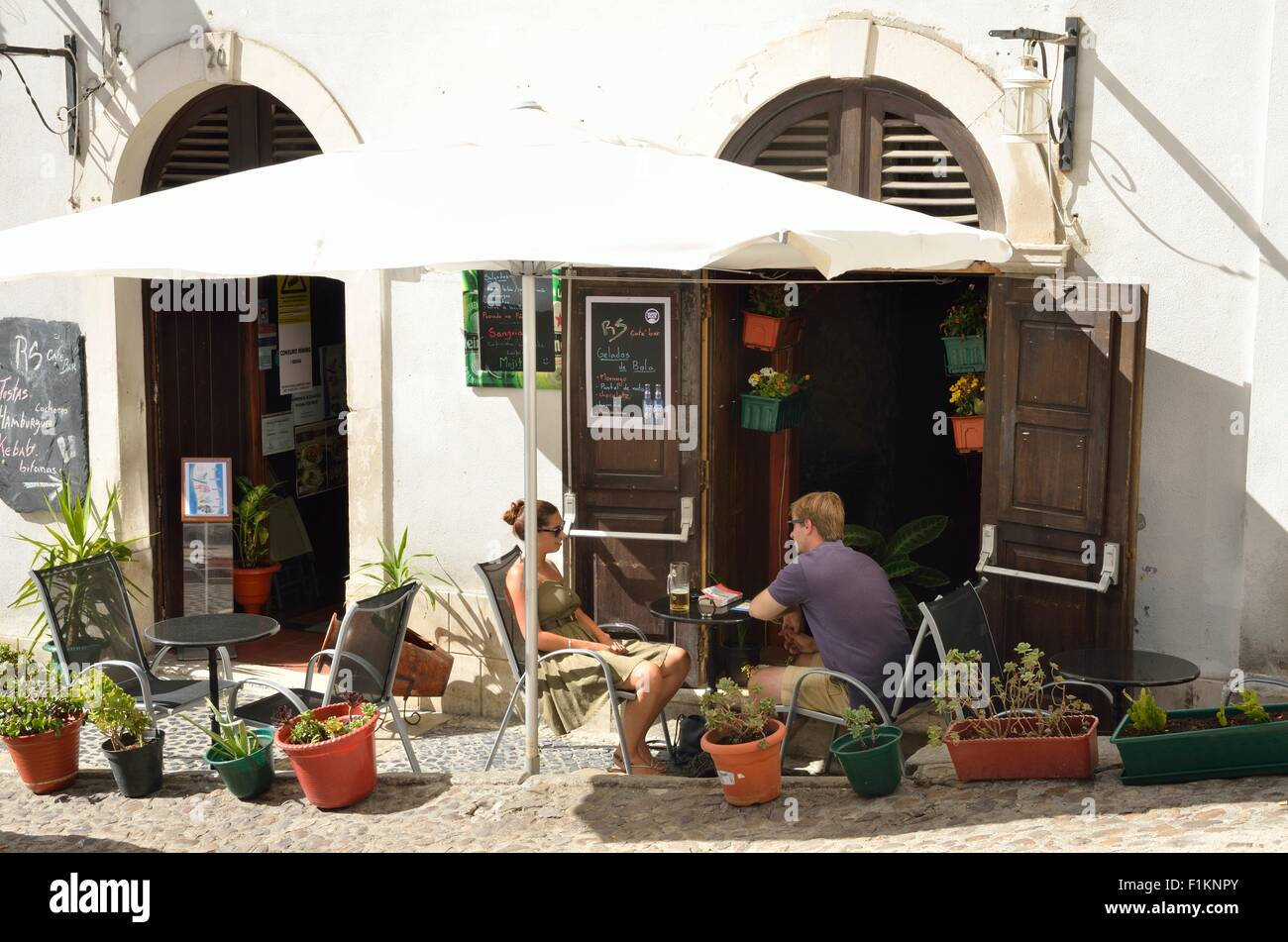 A couple having a beer at an outdoor bar in the city of Coimbra, Portugal - Stock Image