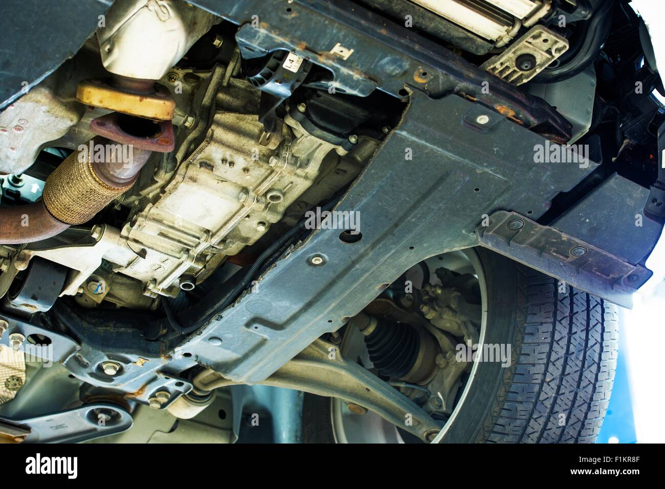 Rusty Car Undercarriage Closeup Photo. Car in Auto Service. Lifted Broken Car. - Stock Image