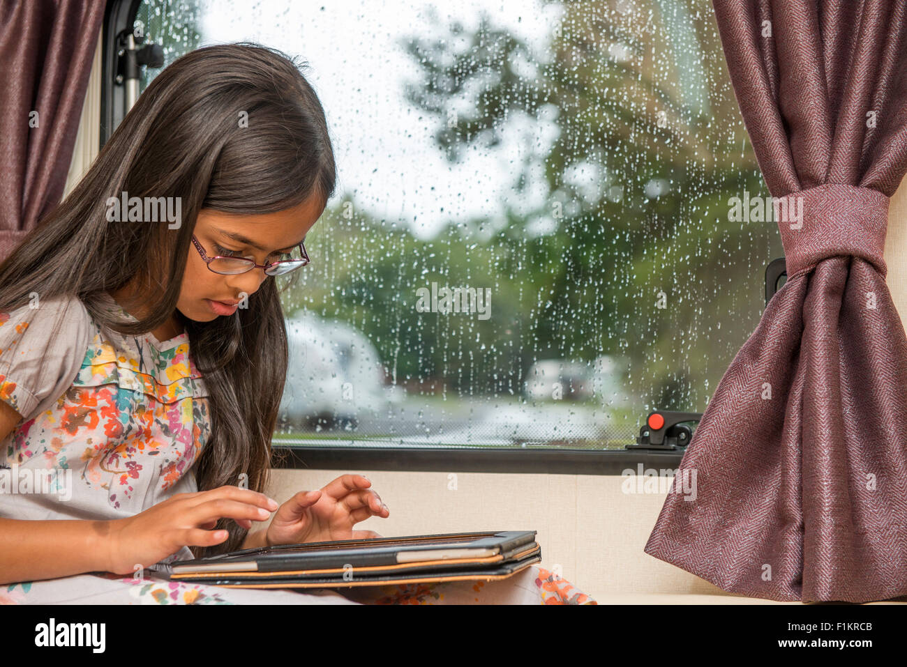 Young girl playing with her I pad, in a rainy day, UK - Stock Image