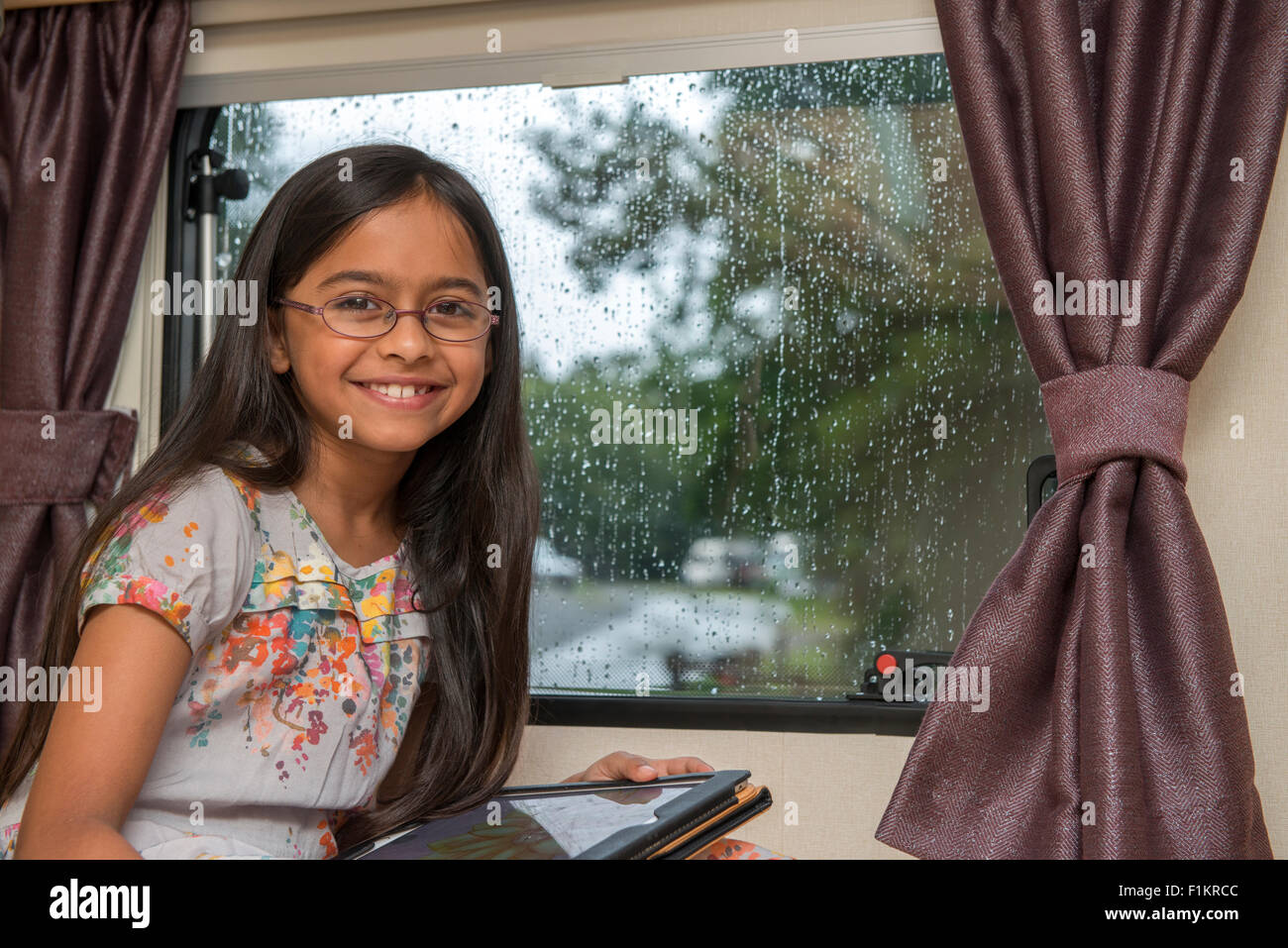 Girl smiling near a caravan window, in a rainy day, UK - Stock Image