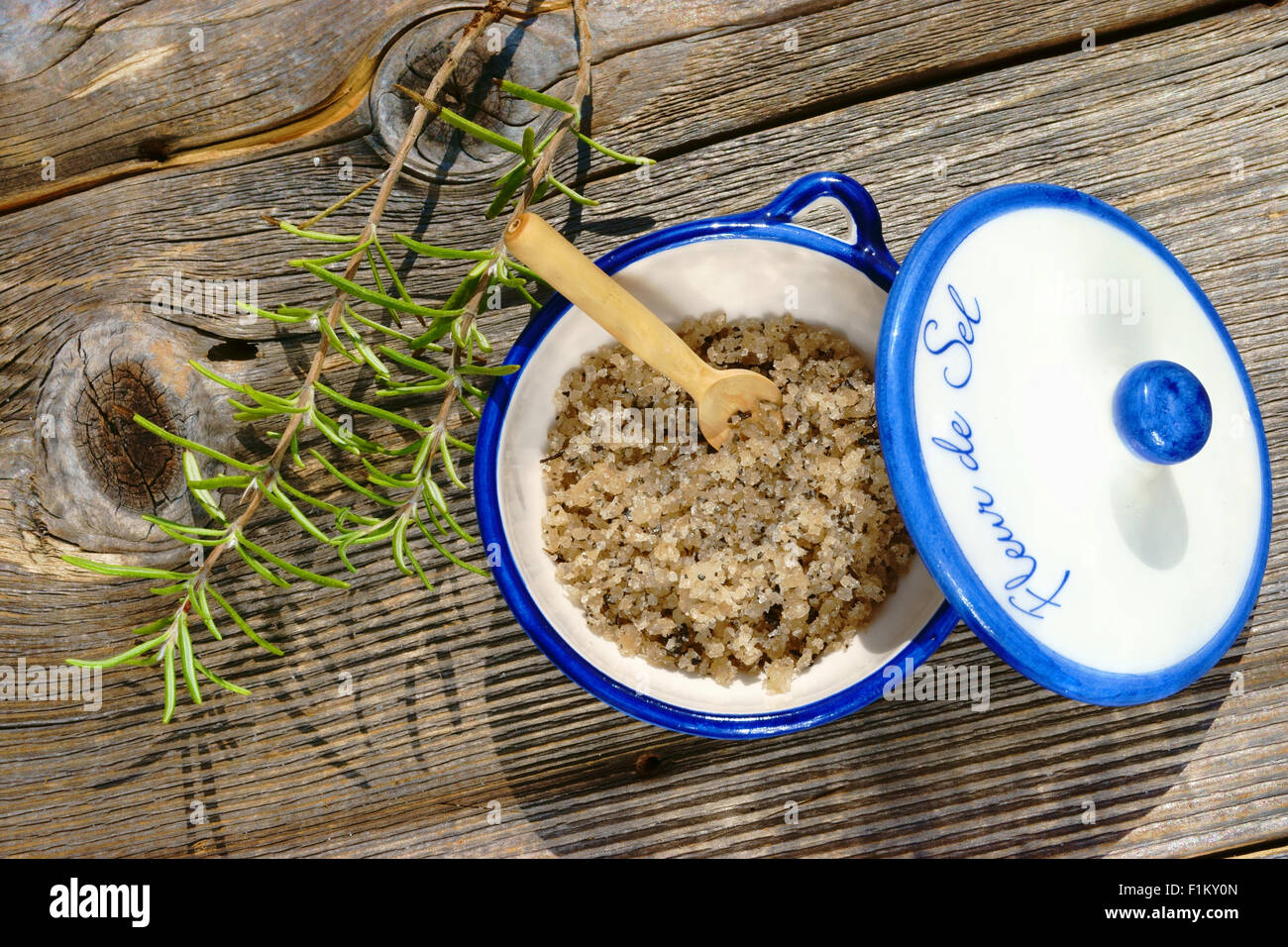 Small porcelain dish with fleur de sel and a rosemary twig on a rustic wooden table - Stock Image