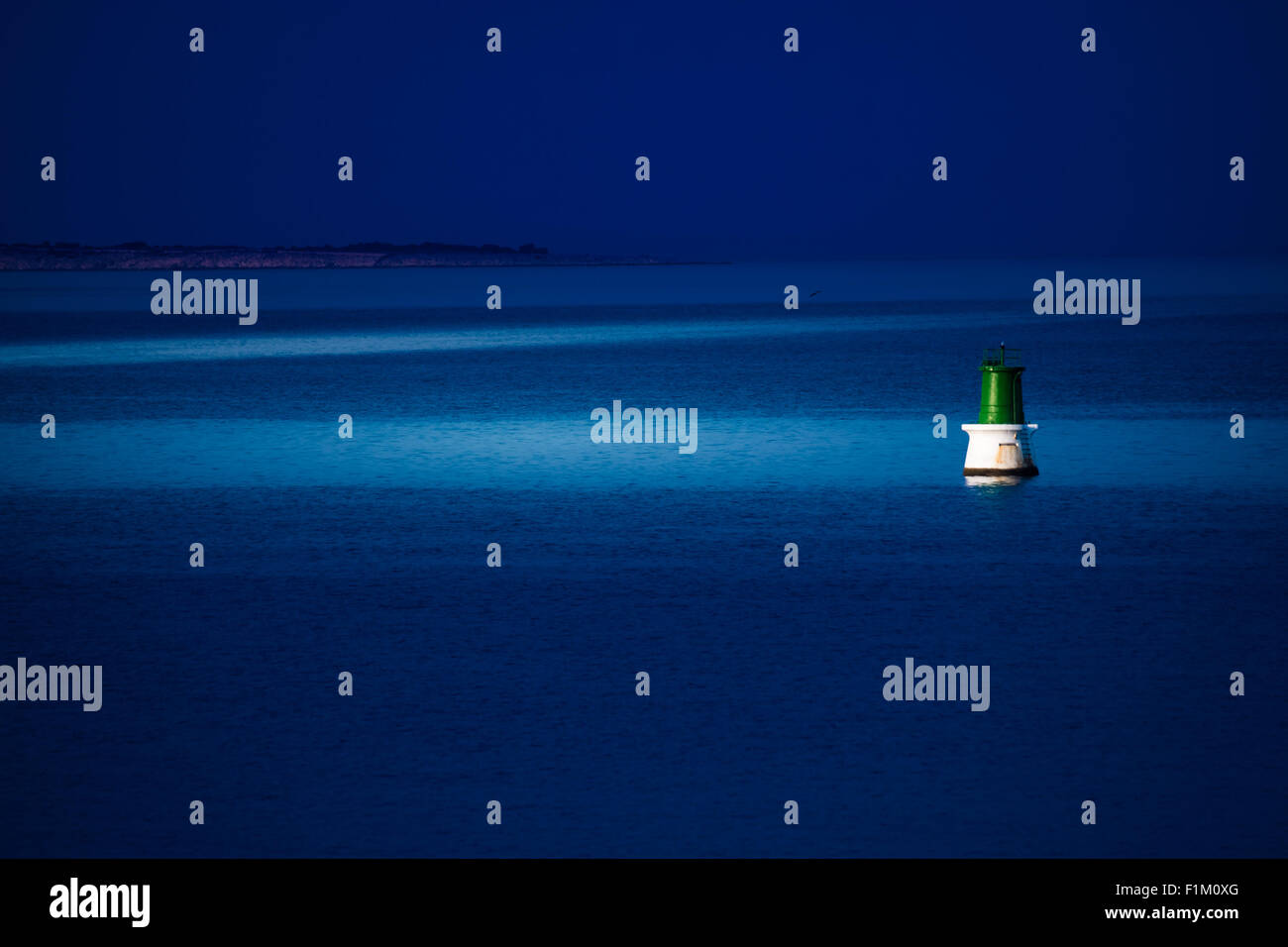 A buoy is reached at night by a patrol boat to be repaired. - Stock Image