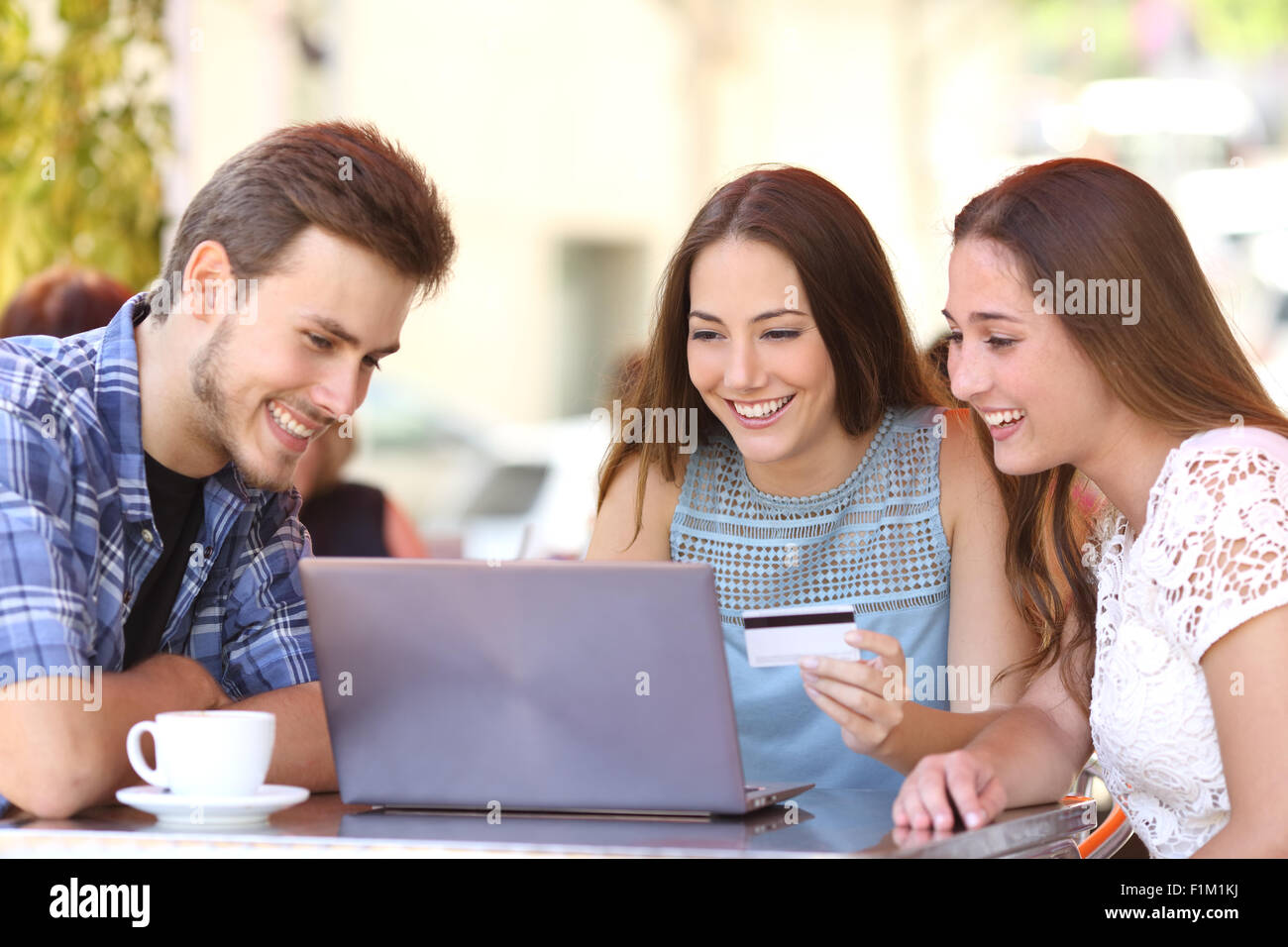 Three happy friends shopping online with a credit card and a laptop in a coffee shop - Stock Image
