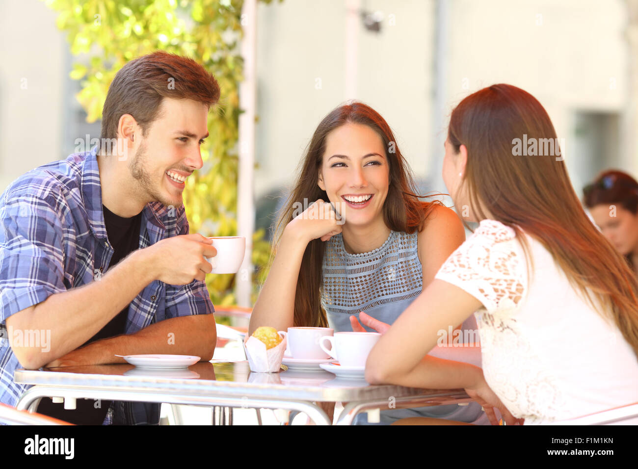 Three happy friends talking and laughing in a coffee shop terrace - Stock Image