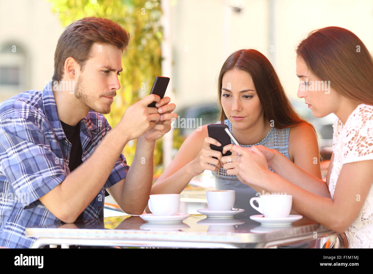 Group of three smart phone addicted friends in a coffee shop terrace everyone with one cellphone - Stock Image