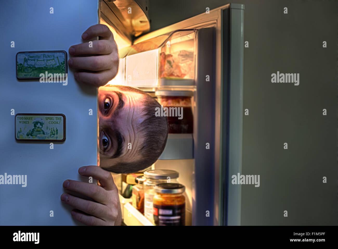 Man emerging form the fridge, image manipulation - Stock Image