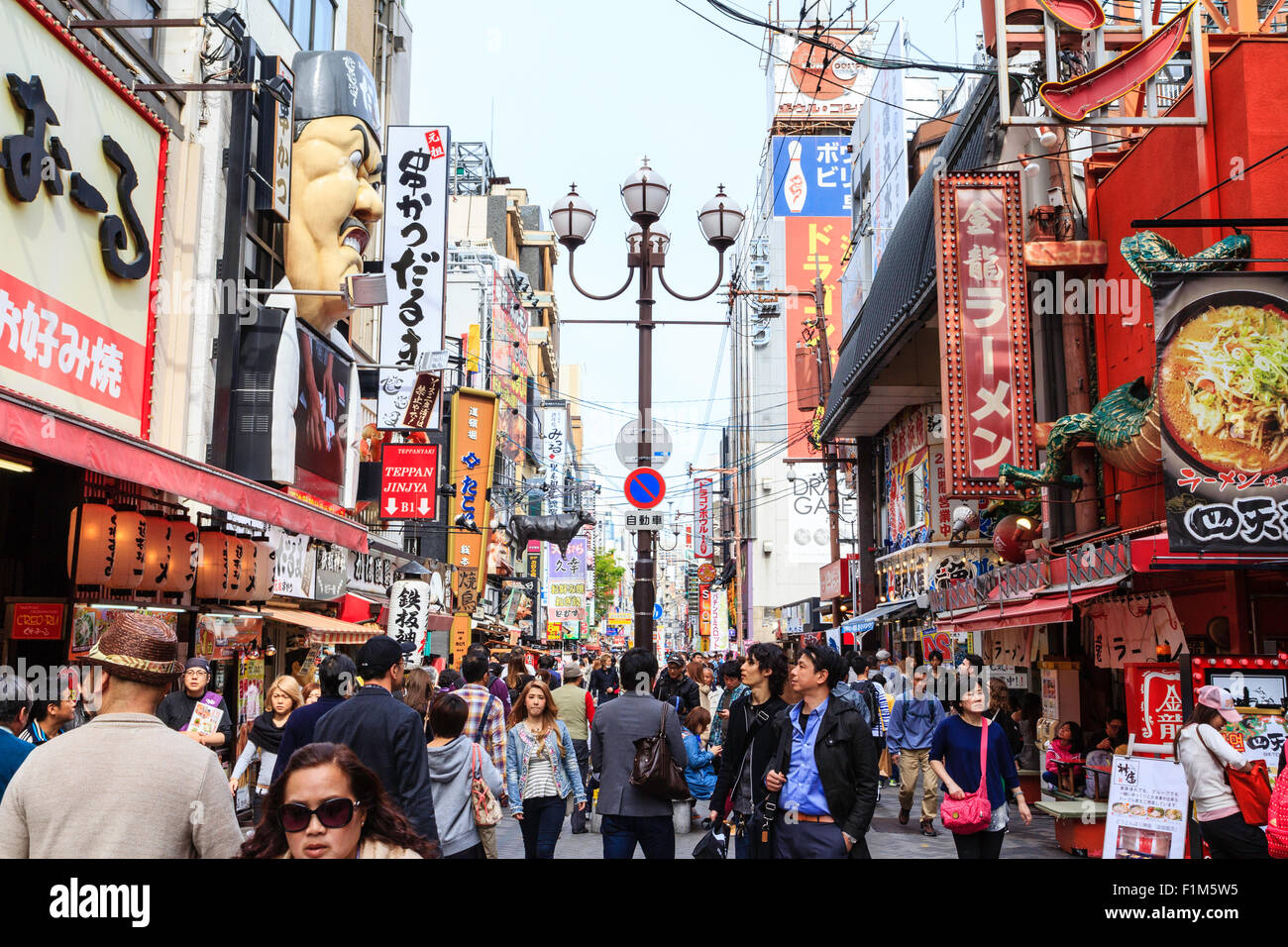 Japan, Osaka. Dotonbori. View along famous street with masses of signs on sides of buildings. Street crowded with - Stock Image