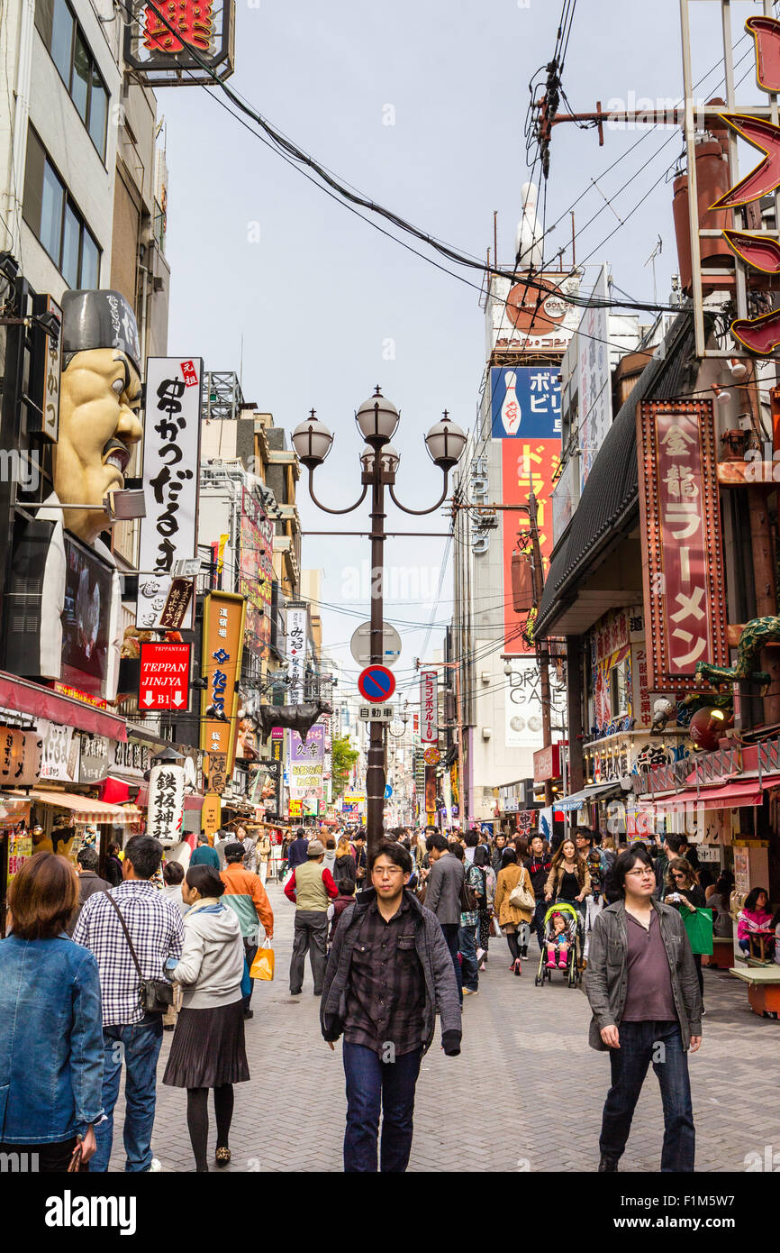 Japan, Osaka, Dotonbori. View along famous street with stores, buildings and signs. Many people and tourists wandering - Stock Image