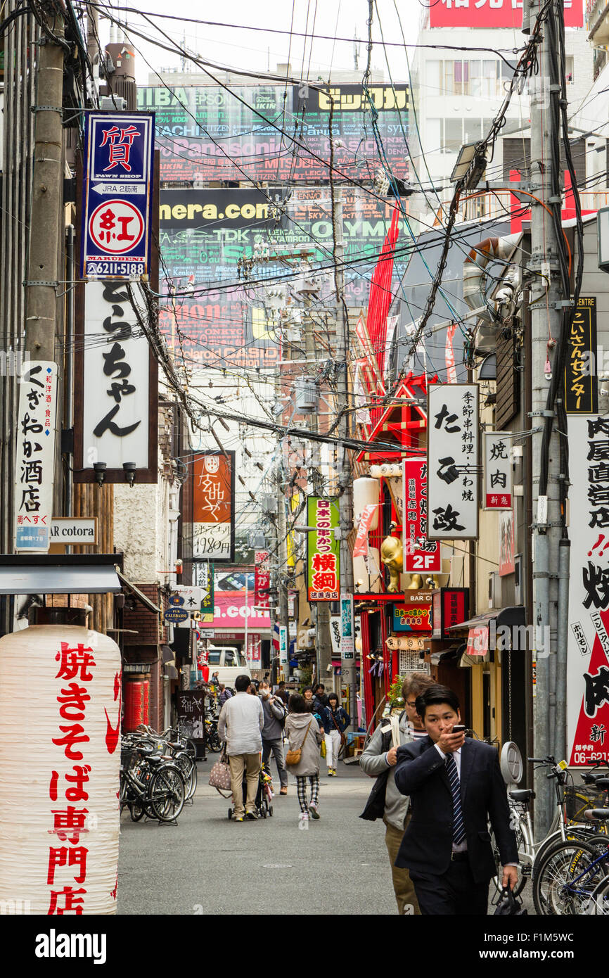 Japan, Osaka, Dotonbori.  View along typical narrow Japanese city street cluttered with signs and overhead wires - Stock Image