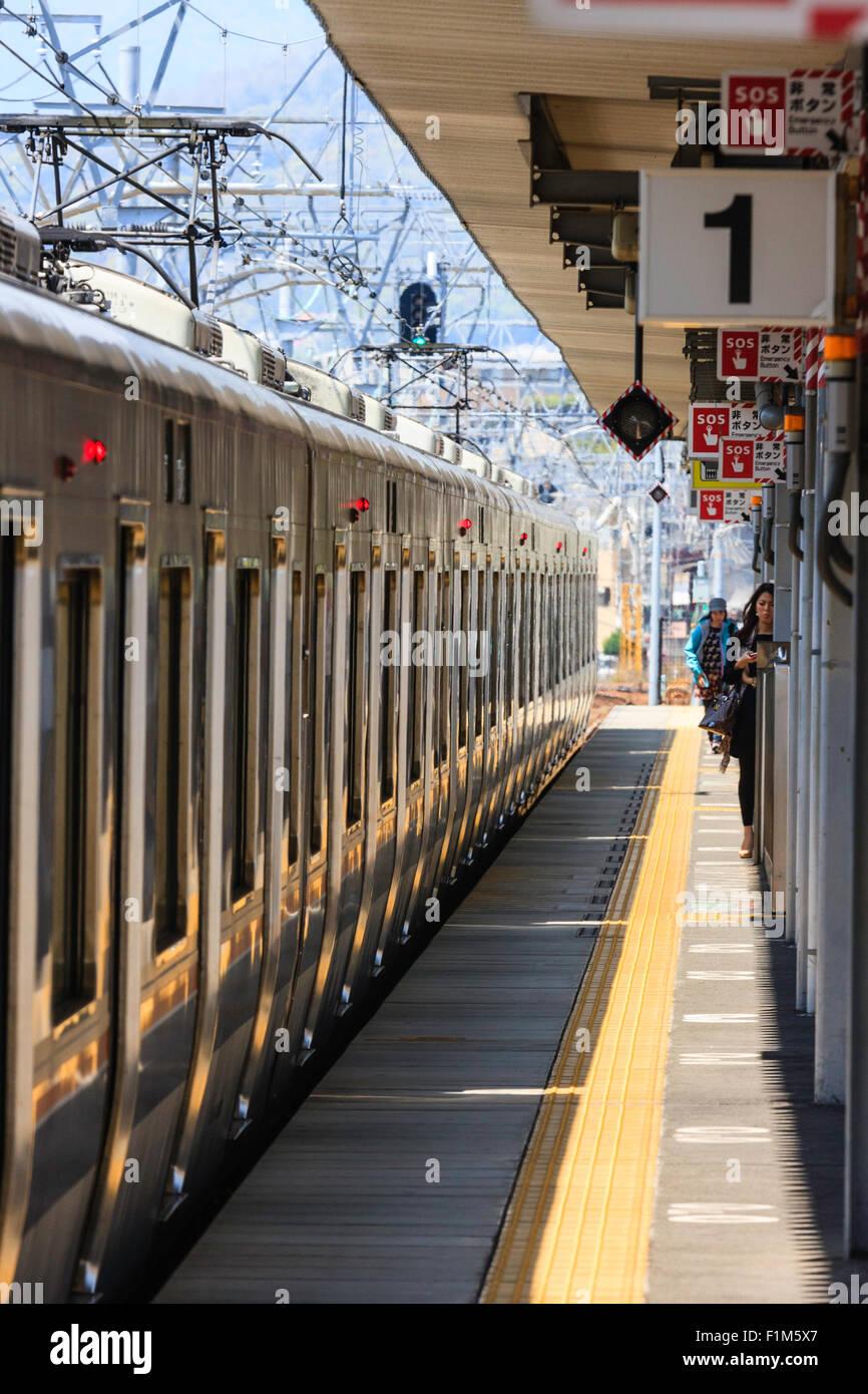 Japan, JR Amagaski, Electric railcar commuter train at platform 1, people boarding - Stock Image